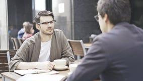 Un homme dans des lunettes écoute son ami au café dehors Image stock