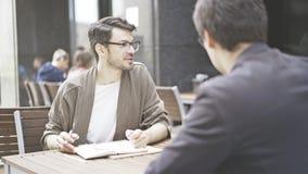 Un homme dans des lunettes parlant écouter son ami au café dehors Images stock