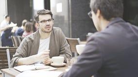 Un homme dans des lunettes parlant écouter son ami au café dehors Photographie stock