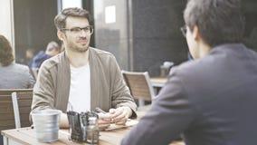 Un homme dans des lunettes parlant écouter son ami au café dehors Image libre de droits