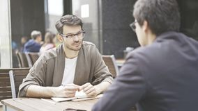 Un homme dans des lunettes parlant écouter son ami au café dehors Photos libres de droits