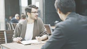 Un homme dans des lunettes parlant écouter son ami au café dehors Photographie stock libre de droits