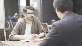 Un homme dans des lunettes parle à son ami au café dehors Photo libre de droits