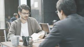 Un homme dans des lunettes regardant dans ses papiers le café dehors Image stock