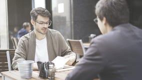 Un homme dans des lunettes regardant dans ses papiers le café dehors Photo stock
