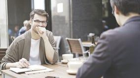 Un homme dans des lunettes riant du café dehors Photos libres de droits