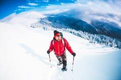 Un homme dans des raquettes dans les montagnes Photo libre de droits