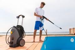 Un homme dans des shorts bleus nettoie une piscine photos libres de droits