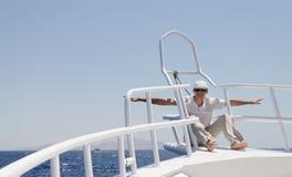 Un homme dans des vêtements lumineux portant un chapeau et des lunettes sur un yacht image stock