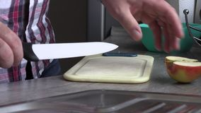 Un homme dans la cuisine coupant en tranches une pomme banque de vidéos
