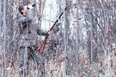 Un homme dans le camouflage et avec un fusil de chasse dans une forêt sur un PS Photos libres de droits