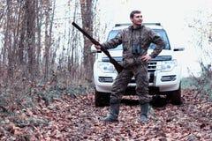 Un homme dans le camouflage et avec un fusil de chasse dans une forêt sur un PS Images stock