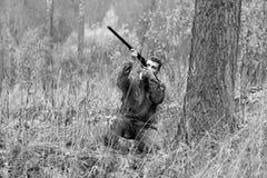 Un homme dans le camouflage et avec un fusil de chasse dans une forêt sur un PS Photographie stock libre de droits