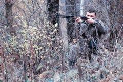 Un homme dans le camouflage et avec un fusil de chasse dans une forêt sur un PS Images libres de droits