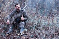 Un homme dans le camouflage et avec un fusil de chasse dans une forêt sur un PS Photo libre de droits