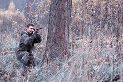 Un homme dans le camouflage et avec un fusil de chasse dans une forêt sur un PS Photographie stock