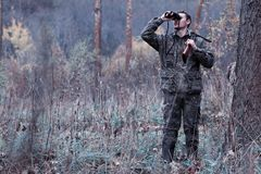 Un homme dans le camouflage et avec un fusil de chasse dans une forêt sur un PS Photos stock