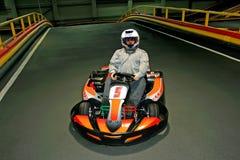 Un homme dans le casque dans le kart sur la karting-voie à l'intérieur image libre de droits