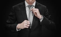 Un homme dans le costume noir attachant la cravate grise sur le fond noir images stock