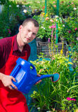 Un homme dans le jardin avec la boîte d'arrosage Photos libres de droits