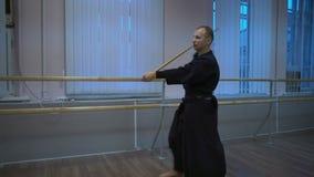 Un homme dans le kimono tient la formation de kendo dans le hall de formation pendant le matin banque de vidéos