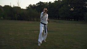 Un homme dans les coups blancs de travaux de kimono donne un coup de pied dedans le style de karaté tôt le matin en parc de ville banque de vidéos