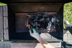 Un homme dans les gants distribue des charbons dans le gril Barbecue d'?t? photos libres de droits