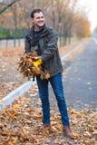 Un homme dans les gants en caoutchouc jaunes enlève les feuilles tombées par automne, en parc photo stock