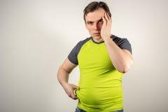 Un homme dans les jeans et un T-shirt avec un gros ventre sur un fond blanc photographie stock libre de droits
