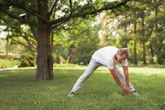 Un homme dans les vêtements de sport légers fait des exercices en parc Photo stock
