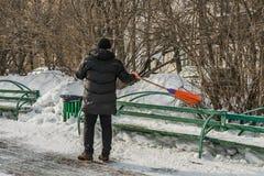 Un homme dans les vêtements noirs et les gants oranges avec un balai orange lumineux en plastique dans des ses mains balaye le ba photographie stock libre de droits