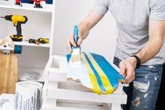 Un homme dans un T-shirt gris peint un panneau de planche ? roulettes dans un atelier et ?coute la musique sur des ?couteurs photographie stock libre de droits