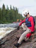 Un homme dans un gilet et un casque de sauvetage s'assied sur une roche Photo libre de droits