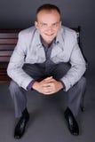 Un homme dans un manteau gris s'assied sur un brun de banc de rue Photos stock