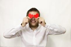 Un homme dans une chemise blanche avec une barbe tient 2 coeurs rouges vis-à-vis de Images libres de droits