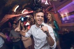 Un homme dans une chemise blanche chante dans une boîte de nuit Il a un microphone dans des ses mains Image stock