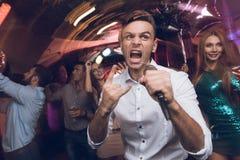Un homme dans une chemise blanche chante dans une boîte de nuit Il a un microphone dans des ses mains Images stock