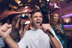 Un homme dans une chemise blanche chante dans une boîte de nuit Il a un microphone dans des ses mains Photo libre de droits