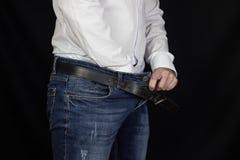 Un homme dans une chemise blanche et des jeans a poussé sa main dans son pantalon et prises sur l'aine, plan rapproché, fond noir images libres de droits