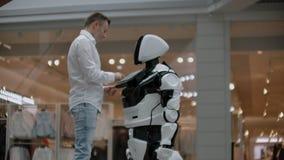 Un homme dans une chemise communique avec un robot blanc posant des questions et pressant l'écran avec ses doigts banque de vidéos