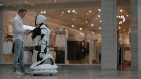Un homme dans une chemise communique avec un robot blanc posant des questions et pressant l'écran avec ses doigts clips vidéos