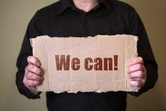 Un homme dans une chemise foncée tenant un morceau de carton avec le texte nous pouvons photographie stock libre de droits