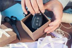 Un homme dans une chemise légère prépare un boîte-cadeau pour les vacances tonalité La voiture comme cadeau Clés de voiture dans  Photographie stock libre de droits