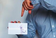Un homme dans une chemise légère tient un boîte-cadeau blanc avec un ruban lilas dans sa main tonalité Images stock