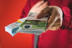 un homme dans une chemise rouge avec une carte tient dans sa main un bouchon des factures sur un fond rouge image stock