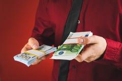 un homme dans une chemise rouge avec une carte tient dans sa main un bouchon des factures sur un fond rouge photo stock