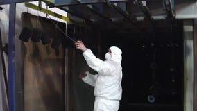 Un homme dans une tenue de protection ouvre les portes au four et apporte là les détails banque de vidéos