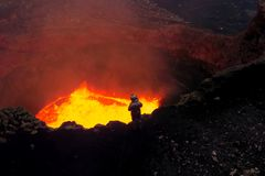 Un homme dans une tenue de protection près de la bouche du volcan avec du magma Magma fondu dans le museau photo stock