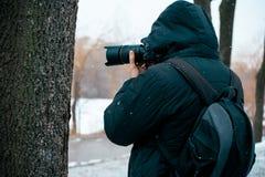 Un homme dans une veste avec un capot et une serviette sur le sien de retour, tenant une caméra photographie stock libre de droits