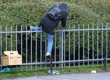 Un homme dans une veste avec un capot s'élève au-dessus d'une barrière image stock